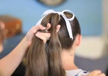 Волосы, собранные в высокий конский хвост, разделяются на 2 равные части